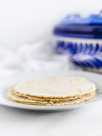 homemade corn tortillas stacked on a plate