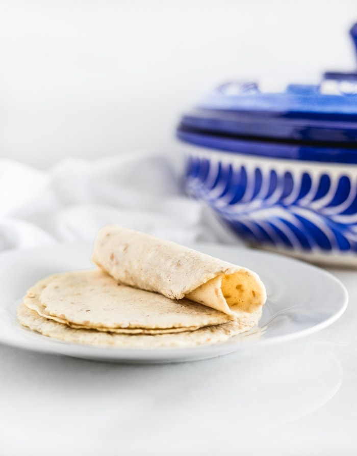 homemade corn tortillas on a plate with one tortilla rolled up