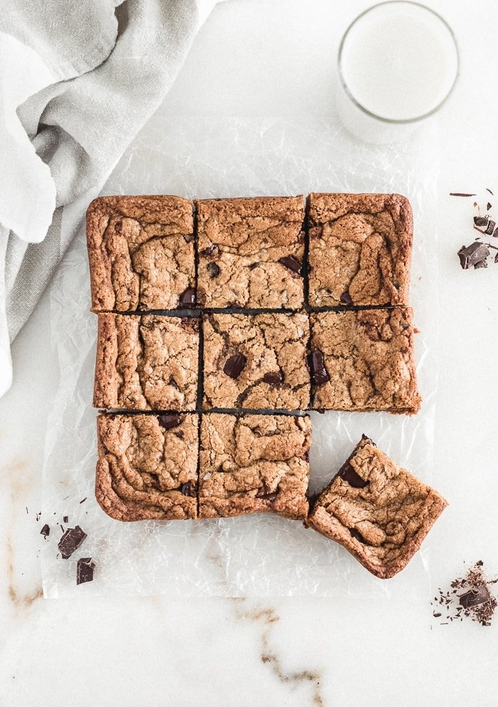 overhead view of chocolate chunk blondies cut into squares surrounded but chocolate chunks, a glass of milk, and a linen napkin.
