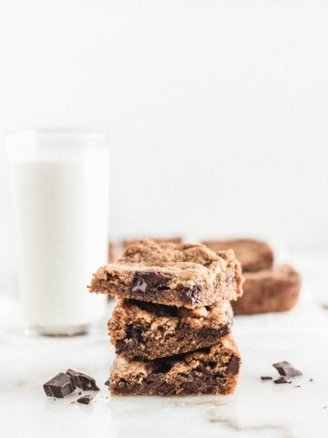 Three chocolate chunk blondies stacked on top of each other with a glass of milk and more blondies in the background.