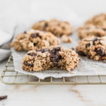gluten free oatmeal chocolate chunk cookie with a bite taken out on a cooling rack covered in parchment.