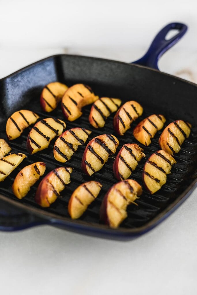 sliced peaches being grilled on a grill pan.