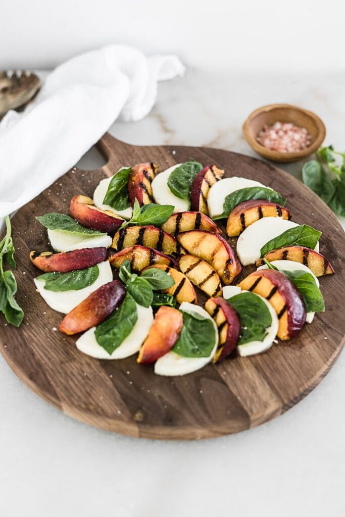 Grilled Peach Caprese salad on a round wooden cutting board with a white linen, basil and bowl of salt in the background.