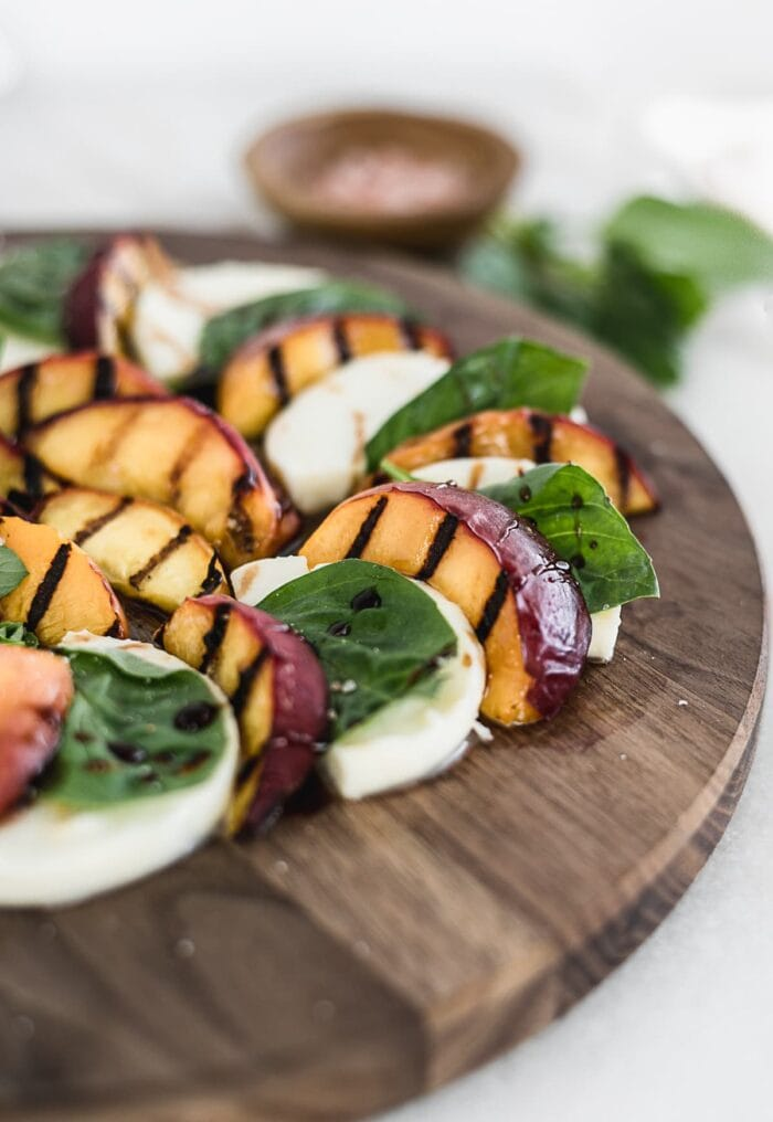 closeup of grilled peach caprese salad on a wooden cutting board.