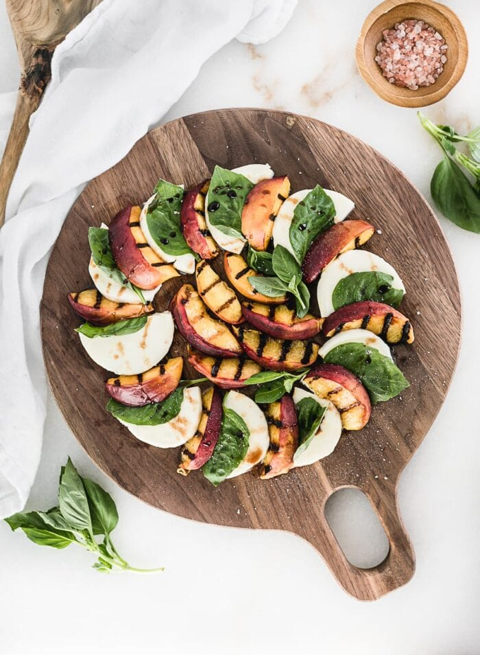 overhead view of grilled peach caprese salad on a round wooden cutting board.