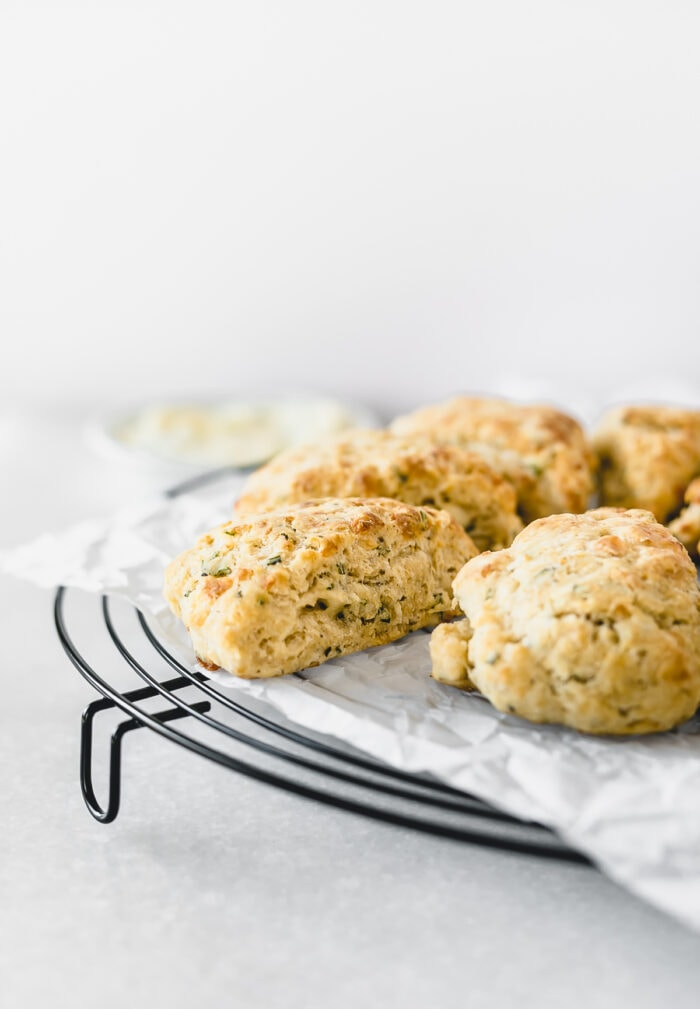closeup of rosemary parmesan scones on top of a parchment lined black cooling rack.