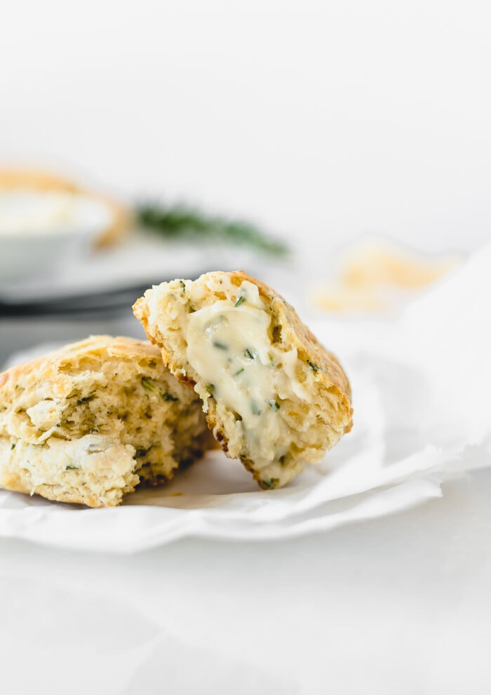 rosemary parmesan scone broken in half and spread with garlic herb butter.