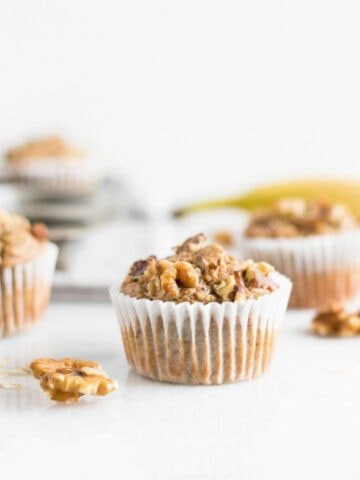 Close up of healthy blender gluten-free banana nut muffin surrounded by walnuts.