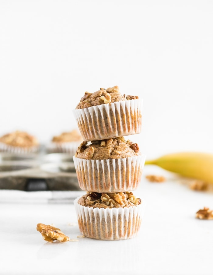 Three healthy blender gluten-free banana nut muffins stacked on top of each other with more muffins behind them.