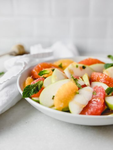 closeup of citrus apple salad in a white bowl topped with fresh mint.