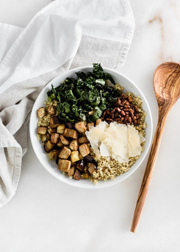 overhead view of prepared ingredients for roasted eggplant kale quinoa salad in a white bowl.