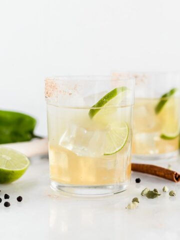 hatch chile margarita in a glass with a lime slice, surrounded by lime and spices.