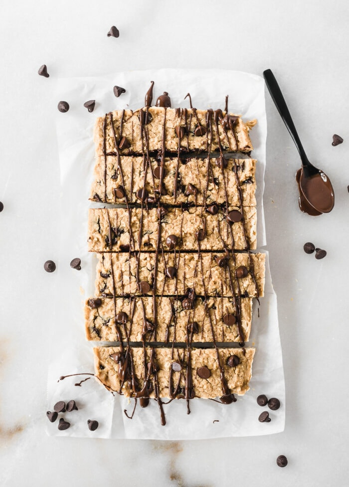 overhead view of chocolate chip cookie chickpea protein bars drizzled with chocolate with a spoon of melted chocolate next to them.