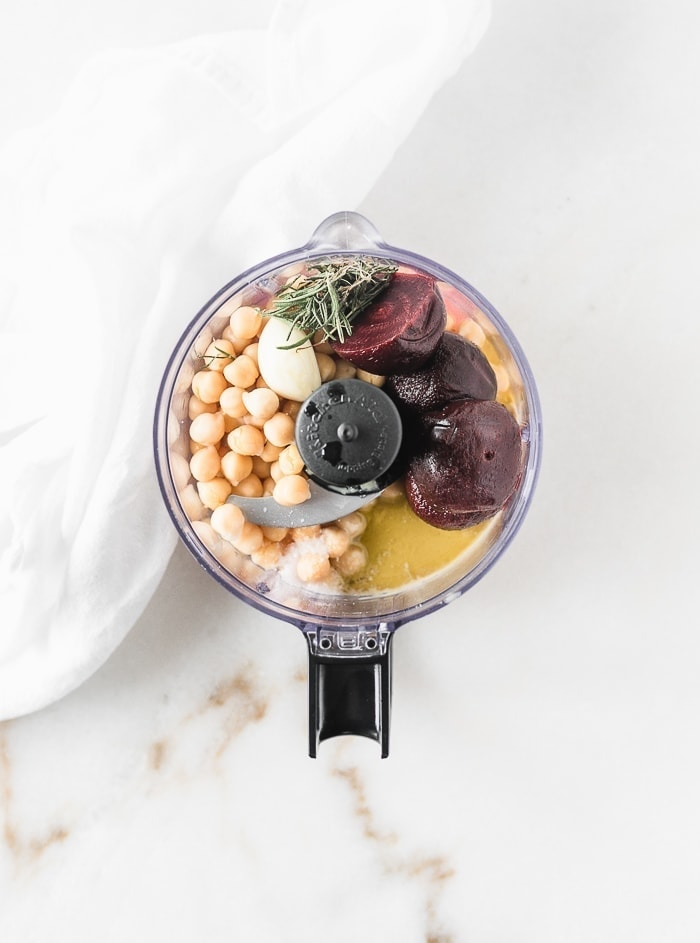chickpeas, roasted beets, rosemary, tahini, lemon juice, oil, and garlic in the bowl of a food processor.