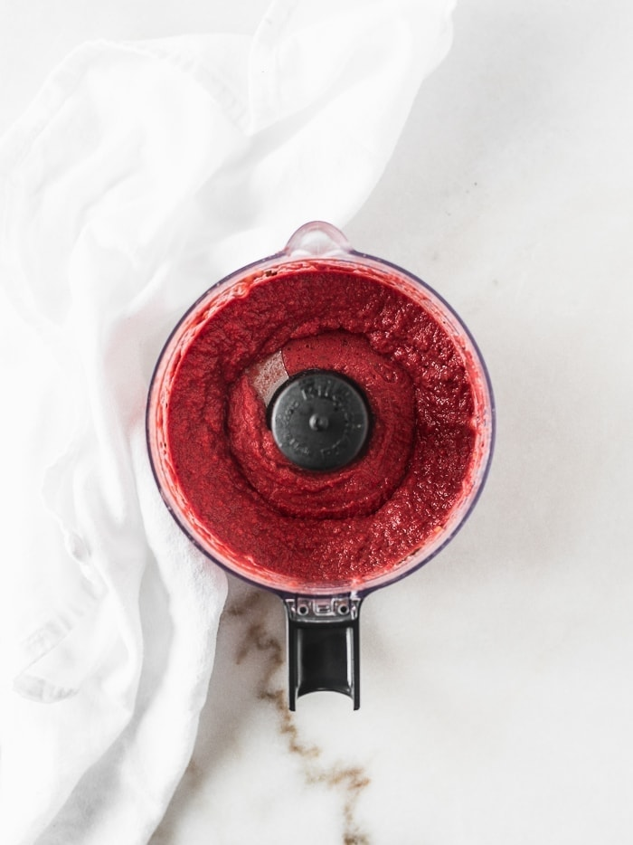 Roasted beet hummus in the bowl of a food processor.