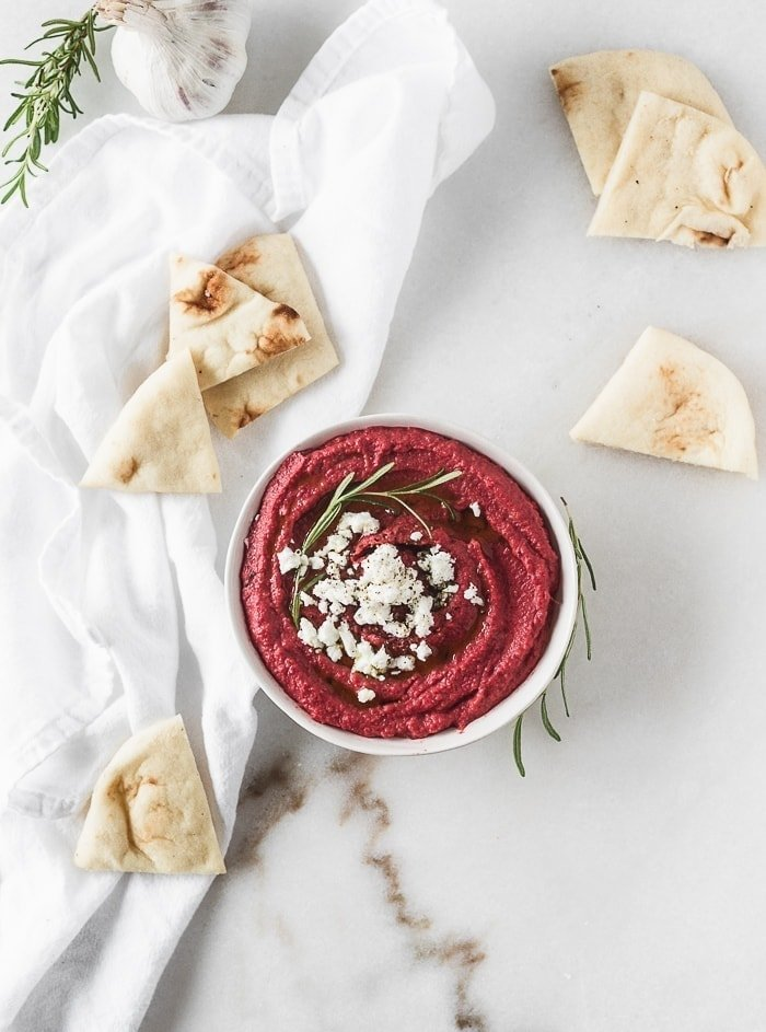 overhead view of roasted beet hummus in a white bowl garnished with rosemary and goat cheese, surrounded by pieces of pita bread.
