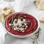 Roasted beet hummus in a white bowl garnished with goat cheese and fresh rosemary.