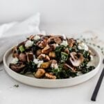 Warm eggplant mushroom kale salad on a white plate.