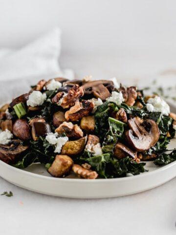 Warm eggplant mushroom kale salad on a white plate.