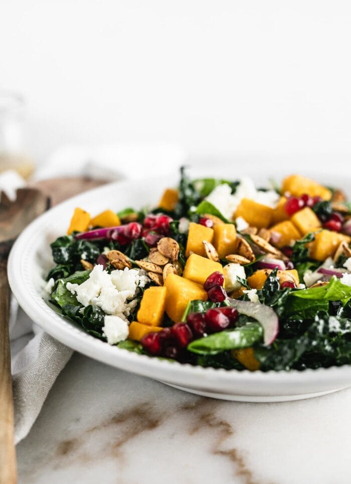 Butternut squash salad with kale, spinach, pomegranate, onions, and feta cheese.