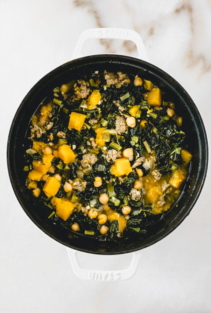 Overhead view of Sausage, Kale and Butternut Squash Soup in a white dutch oven.