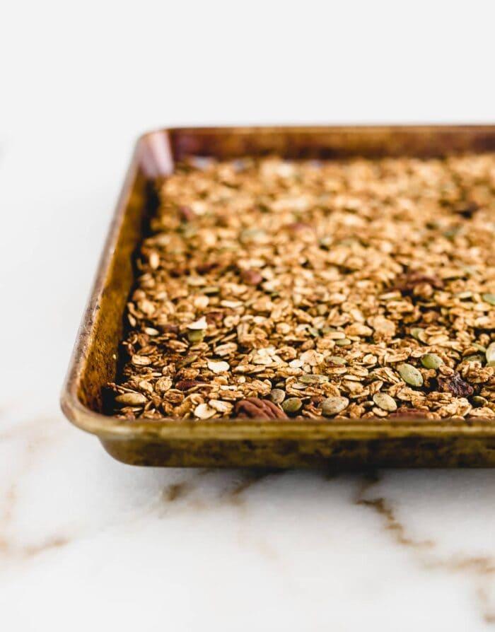 Chunky pumpkin granola on a baking sheet.
