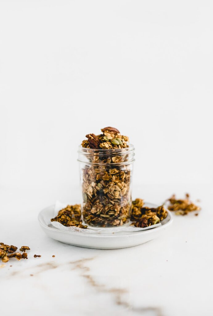 Chunky pumpkin granola in a clear container on a plate.