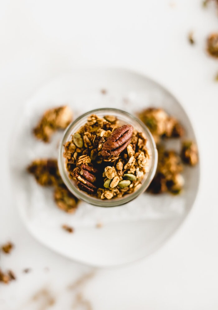 overhead view of pumpkin granola in a glass jar on top of a plate surrounded by granola chunks.
