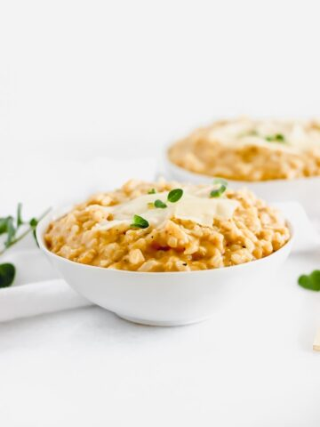 pumpkin risotto in a white bowl topped with parmesan cheese and herbs.
