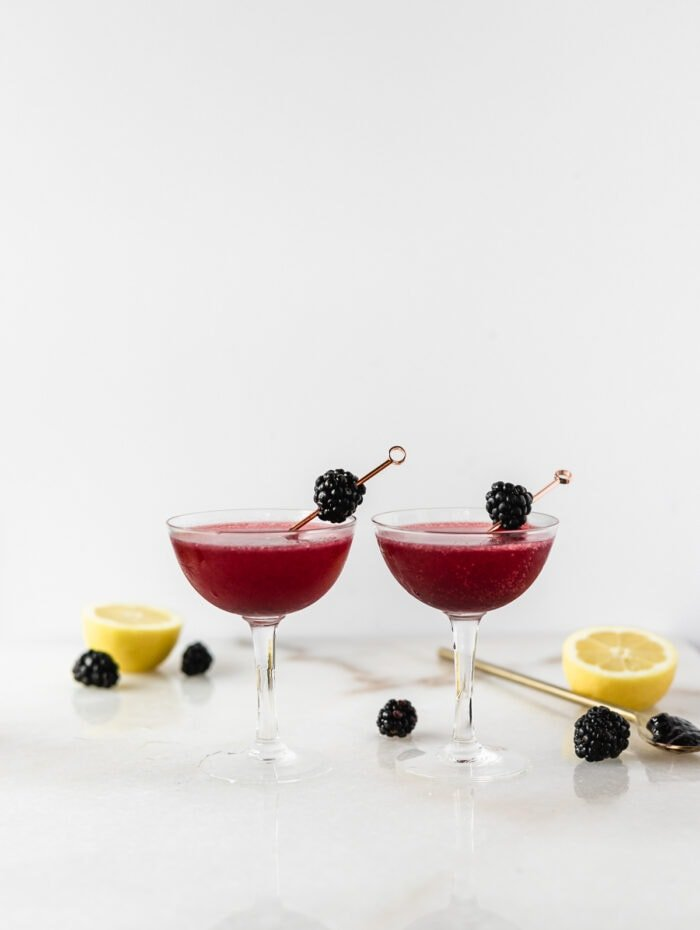 two side by side blackberry gin and jam cocktails in coupe classes surrounded by lemons, blackberries and a spoon of blackberry jam.