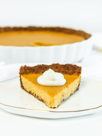 A slice of butternut squash tart with whipped cream on top on a white plate with more pie behind it.