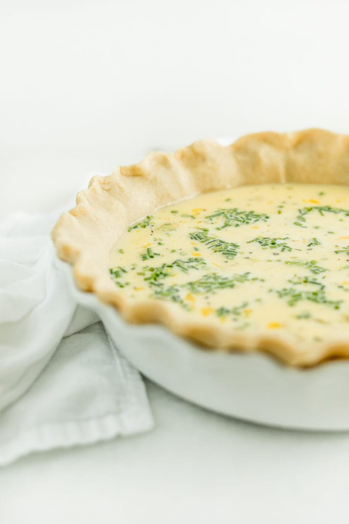 unbaked eggs benedict quiche in a white pie dish.