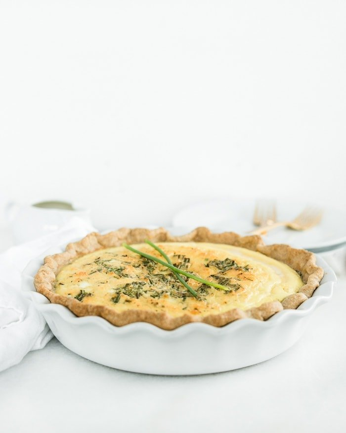 Eggs Benedict Quiche in a white pie dish with white plates and gold forks in the background.