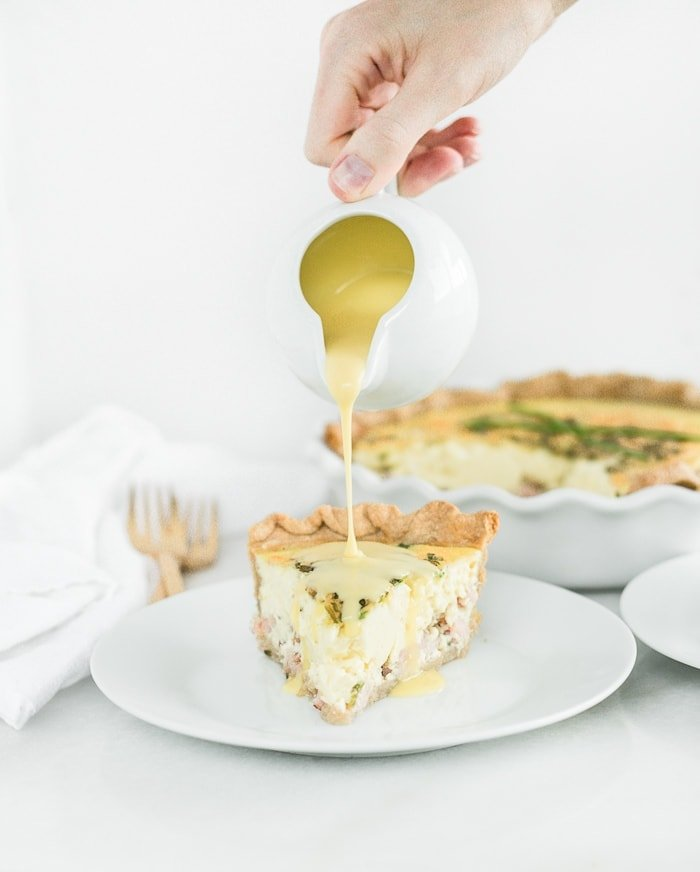 hand pouring hollandaise sauce over a slice of eggs benedict quiche on a white plate.