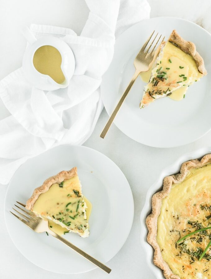 Overhead view of two slices of Eggs Benedict Quiche on white plates with gold forks, a pouring dish of hollandaise sauce, and a pie dish of quiche.