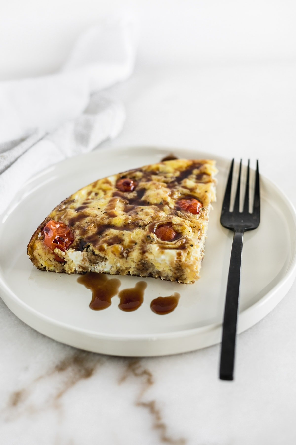 A slice of Italian sausage and tomato frittata on a white plate.