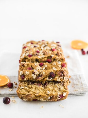 Healthy cranberry orange oatmeal bread with a few slices cut off the loaf on top of a napkin.