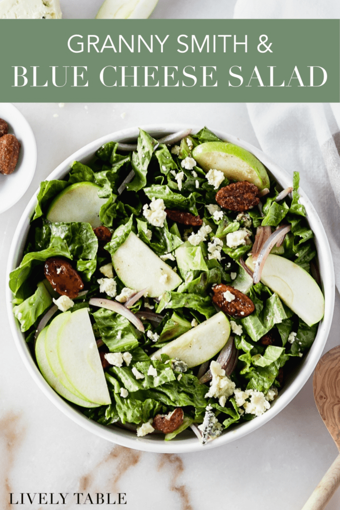 overhead view of a salad with romaine, granny smith apple slices, blue cheese, red onions and pecans in a white bowl with text overlay.