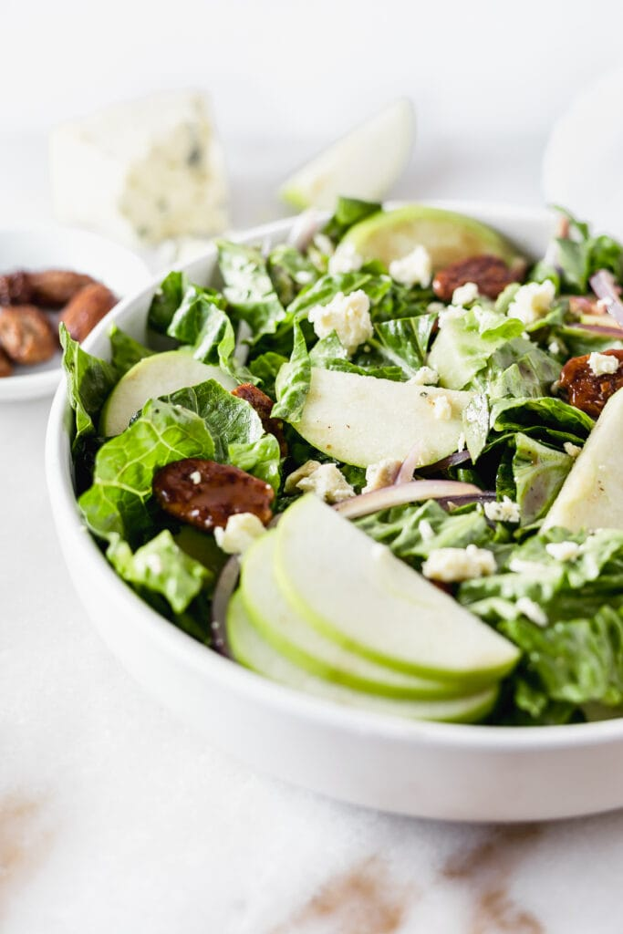 closeup of a romaine salad with granny smith apple slices and blue cheese.