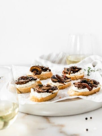 Closeup of a mushroom ricotta crostini on a white napkin with more behind it.
