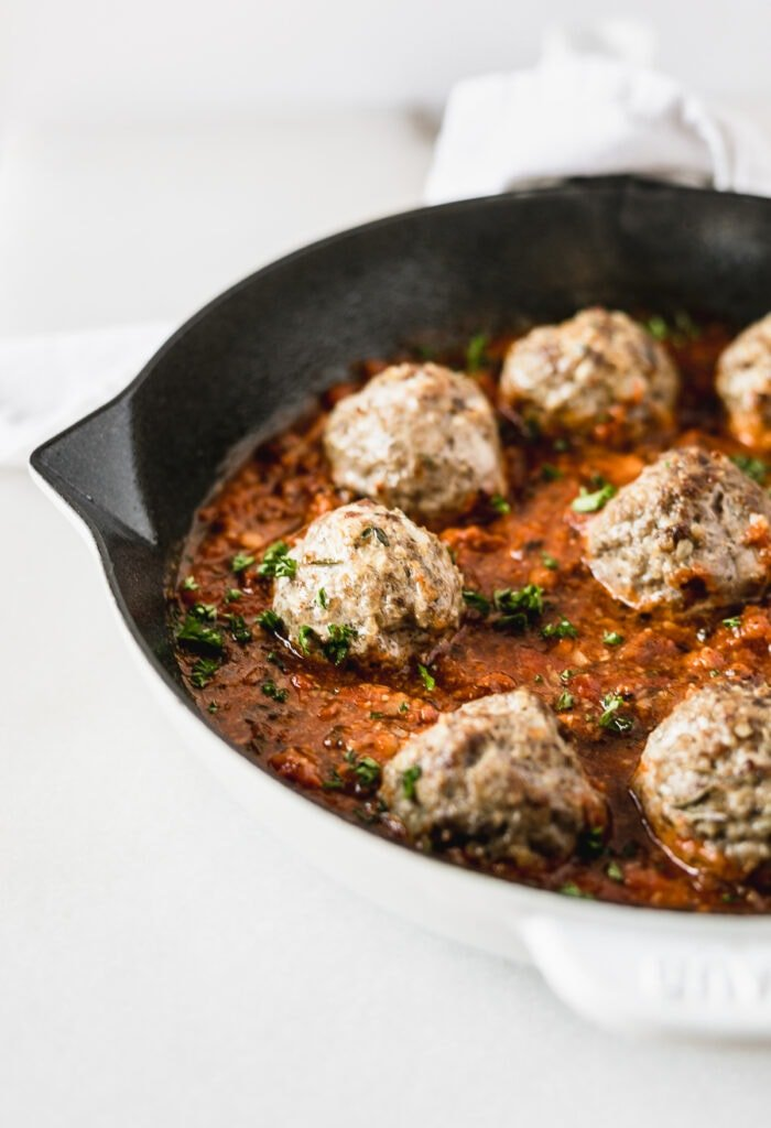 closeup of beef and quinoa meatballs with tomato sauce in a white skillet.