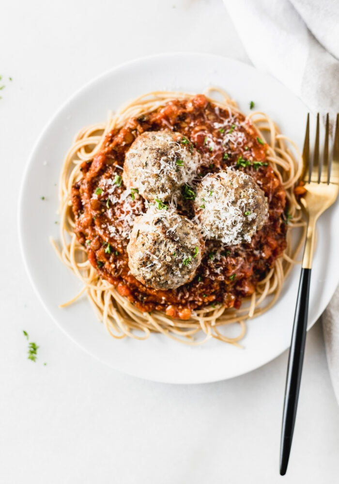 overhead view of a plate of spaghetti with three beef and quinoa meatballs sprinkled with cheese and parsley with a black and gold fork.