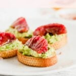 Blood Orange Avocado Crostini are tiny versions of everyone's favorite snack topped with beautiful blood oranges, honey and sea salt.They're a delicious and healthy appetizer! (#vegetarian) #bloodorange #citrus #avocado #toast #crostini #appetizer #snack #brunch