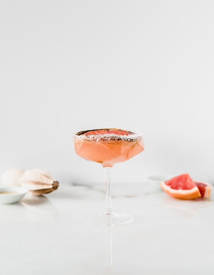 broiled grapefruit paloma with sugar on the rim with a citrus reamer and grapefruit wedges in the background.