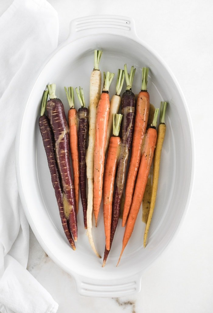 overhead view of rainbow carrots in a white oval baking dish with maple dijon sauce poured on the top.