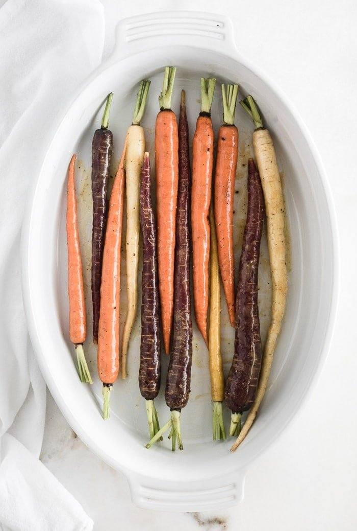 rainbow carrots in a white oval baking dish before roasting.