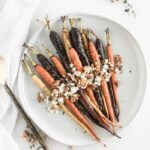 Overhead view of maple dijon roasted carrots with goat cheese, walnuts and thyme on a white plate.