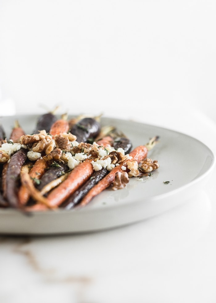 Maple dijon roasted carrots with goat cheese, walnuts and thyme on a grey plate with a closeup of the goat cheese walnut topping.