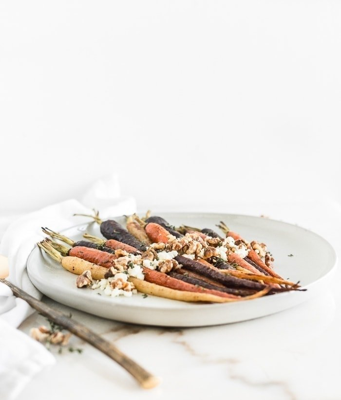 Maple dijon roasted carrots with goat cheese, walnuts and thyme on a white plate.