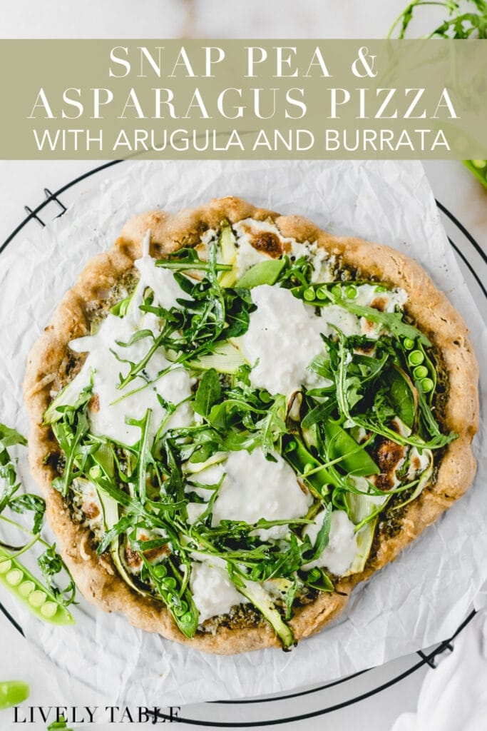 overhead view of asparagus snap pea pizza with burrata and arugula on a wire cooling rack lined with parchment with text overlay.